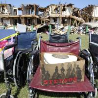 Photo - A Stetson hat rests on a wheelchair outside the apartment complex adjacent to the site of the fire and explosion in West, Texas on Wednesday, April 24, 2013. The explosion at West Fertilizer which killed 14 people left a crater more than 90 feet (27 meters) wide and blasted the walls and windows off dozens of buildings in the town of 2,700. (AP Photo/The San Antonio Express-News, Tom Reel, Pool)