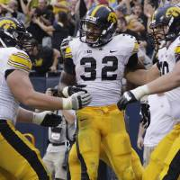 Photo -   Iowa running back Andre Dawson (32) celebrates with offensive linemen Austin Blythe (63) and Matt Tobin (60) after scoring a touchdown during the second half of an NCAA college football game against Northern Illinois at Soldier Field in Chicago, Saturday, Sept. 1, 2012. Iowa won 18-17. (AP Photo/Nam Y. Huh)