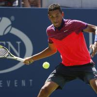 Photo - Nick Kyrgios, of Australia, returns a shot against Mikhail Youzhny, of Russia, during the opening round of the 2014 U.S. Open tennis tournament, Monday, Aug. 25, 2014, in New York. (AP Photo/Frank Franklin II)