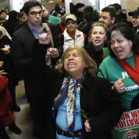 Photo - FILE - In this Jan. 7, 2013 file photo, supporters of granting illegal immigrants drivers licenses cheer after a House committee hearing at the Illinois State Capitol in Springfield. The House passed the legislation Jan. 8 and Gov. Pat Quinn is expected to sign the legislation Sunday, Jan. 27. As Illinois becomes the fourth and most populous state to issue driver's licenses to illegal immigrants, the initiative is still nagged by concerns it has enough safeguards to avoid the identity fraud and other pitfalls faced by the three other states with similar laws. (AP Photo/Seth Perlman, File)