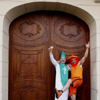 Photo -   An Irish fan with a Dutch fan celebrate in the centre of Proznan on the eve of the Euro 2012 soccer championship Group C match between Ireland and Croatia in Poznan, Poland, Saturday, June 9, 2012. (AP Photo/Peter Morrison)