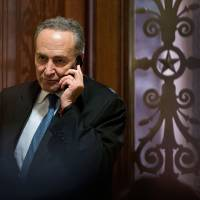 Photo - Sen. Charles Schumer, D-N.Y., third ranking in the Senate Democratic leadership, speaks on his cell phone following a closed-door caucus at the Capitol in Washington, Sunday, Dec. 30, 2012 to discuss how to avoid the