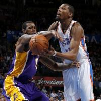 Photo - Oklahoma City's Kevin Durant (35) is fouled by Earl Clark (6) during an NBA basketball game between the Oklahoma City Thunder and the Los Angeles Lakers at Chesapeake Energy Arena in Oklahoma City, Tuesday, March. 5, 2013. Photo by Bryan Terry, The Oklahoman