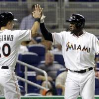 Photo - Miami Marlins' Justin Ruggiano (20) and Marcell Ozuna, right, high-five after scoring on a single by Nick Green in the eighth inning during a baseball game against the Philadelphia Phillies in Miami, Monday, May 20, 2013. The Marlins defeated the Phillies 5-1. (AP Photo/Lynne Sladky)