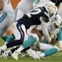 Photo - Miami Dolphins quarterback Ryan Tannehill (17) is sacked by San Diego Chargers free safety Eric Weddle (32) during the first half of an NFL football game, Sunday, Nov. 17, 2013, in Miami Gardens, Fla. (AP Photo/Wilfredo Lee)