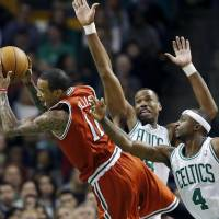 Photo - Boston Celtics' Jason Collins, center, fouls Milwaukee Bucks' Monta Ellis (11) as the Celtics' Jason Terry (4) defends in the second quarter of an NBA basketball game in Boston, Friday, Dec. 21, 2012. (AP Photo/Michael Dwyer)