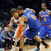 Photo - New York Knicks center Tyson Chandler (6) steals the ball from Atlanta Hawks shooting guard Kyle Korver in the first half of an NBA basketball game Saturday, Feb. 22, 2014, in Atlanta. (AP Photo/John Bazemore)