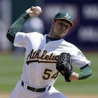 Photo - Oakland Athletics' Sonny Gray works against the Seattle Mariners in the first inning of a baseball game Sunday, April 6, 2014, in Oakland, Calif. (AP Photo/Ben Margot)