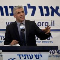 Photo - Yair Lapid gestures as he delivers a speech at  his