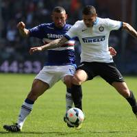 Photo - Sampdoria defender Angelo Palombo, left, and Inter Milan forward Mauro Emanuel Rivero Icardi battle for the ball during a Serie A soccer match, in Genoa, Italy, Sunday, April 13, 2014. (AP Photo/Carlo Baroncini)