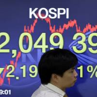 Photo - A currency trader walks by a screen showing the Korea Composite Stock Price Index (KOSPI) at the foreign exchange dealing room of the Korea Exchange Bank headquarters in Seoul, South Korea, Wednesday, Sept. 3, 2014. Asian stock markets rose Wednesday, lifted by new signs of strength in the U.S. economy and expectations that Europe's central bank will provide more support to the flagging region. (AP Photo/Lee Jin-man)