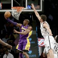 Photo - Los Angeles Lakers' Kobe Bryant, left, puts up a shot underneath the basket while Brooklyn Nets' Brook Lopez defends during the first half of the NBA basketball game at the Barclays Center Tuesday, Feb. 5, 2013 in New York. (AP Photo/Seth Wenig)