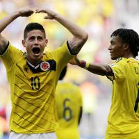 Photo - Colombia's James Rodriguez (10) celebrates with teammate Colombia's Juan Cuadrado after scoring his side's first goal during the group C World Cup soccer match between Colombia and Ivory Coast at the Estadio Nacional in Brasilia, Brazil, Thursday, June 19, 2014. (AP Photo/Fernando Llano)