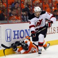 Photo -   New Jersey Devils' Adam Larsson, right, leaves Philadelphia Flyers' Max Talbot down on the ice after a check as he goes after the puck during the second period in Game 2 of an NHL hockey Stanley Cup second-round playoff series, Tuesday, May 1, 2012, in Philadelphia. (AP Photo/Tom Mihalek)