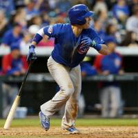 Photo - Chicago Cubs' Chris Coghlan follows the flight of his RBI-double against the Colorado Rockies in the fifth inning of a baseball game in Denver on Wednesday, Aug. 6, 2014. (AP Photo/David Zalubowski)