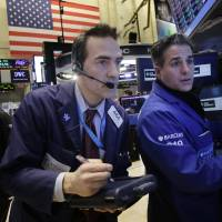 Photo -  Gregory Rowe, center, places orders for stock with Anthony Rinaldi, right, on Wednesday at the New York Stock Exchange. U.S. stocks are edging higher in early trading as the market extends its longest winning streak of the year. AP Photo   Mark Lennihan -  AP