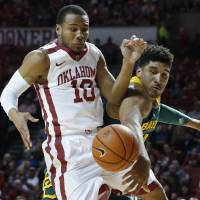 Photo - Baylor guard Ish Wainright, right, knocks the ball away from Oklahoma guard Jordan Woodard (10) in the first half of an NCAA college basketball game in Norman, Okla., Saturday, Feb. 8, 2014. (AP Photo/Sue Ogrocki)