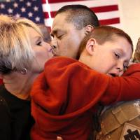 Photo - Sgt. Evan Wallace with the 45th Infantry Brigade kisses his wife Gaylene, while his 4-year-old grandson Landon hugs him, upon his return in April from deployment to Kuwait and Afghanistan. OKLAHOMAN ARCHIVES  Jim Beckel