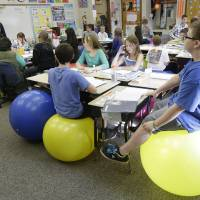 Photo - Robbi Giuliano teaches her fifth grade class as they sit on yoga balls at Westtown-Thornbury Elementary School Monday, Feb. 4, 2013, in West Chester, Pa.  Replacing stationary seats with inflatable bouncers has raised productivity in her fifth-graders at Westtown-Thornbury Elementary School, making students better able to focus on lessons while improving their balance and core strength, she said.   (AP Photo/Matt Rourke)