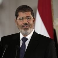 Photo -   FILE - In this Friday, July 13, 2012 file photo, Egyptian President Mohammed Morsi speaks to reporters during a joint news conference with Tunisian President Moncef Marzouki, unseen, at the Presidential palace in Cairo, Egypt. Egypt's Islamist president may hail from the fiercely anti-Israeli Muslim Brotherhood, but in his first major crisis over Israel, he is behaving much like his predecessor, Hosni Mubarak:. He recalled the ambassador and engaged in empty rhetoric supporting Palestinians. Mohammed Morsi is under pressure at home to do more but he is just as wary as Mubarak about straining ties with the United States. (AP Photo/Maya Alleruzzo, File)