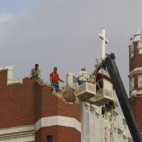 Photo - In this Nov. 6, 2011 file photo, maintenance workers inspect the damage to one of the spires on Benedictine Hall at St. Gregory's University in Shawnee. AP Photo/Sue Ogrocki  Sue Ogrocki