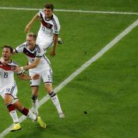 Photo - Germany's Mario Goetze, left, celebrates scoring his side's first goal during the World Cup final soccer match between Germany and Argentina at the Maracana Stadium in Rio de Janeiro, Brazil, Sunday, July 13, 2014. (AP Photo/Fabrizio Bensch, Pool)