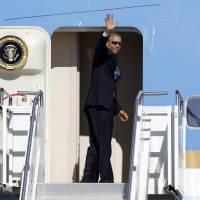 Photo - President Barack Obama waves in the direction of members of the media as he boards Air Force One at Palm Springs International Airport, Saturday, June 14, 2014, in Palm Springs, Calif. Obama is traveling to Orange County to deliver the commencement address for graduates at the University of California, Irvine at Angel Stadium in Anaheim, Calif.  (AP Photo/Alex Gallardo)