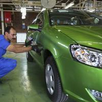 Photo - Iranian car worker Iraj Zarouri inspects a car before it's exported to Russia for the first time since 2009, at the state-run Iran-Khodro automobile manufacturing plant near Tehran, Iran, Sunday, June 29, 2014. Iran began exporting automobiles to Russia for the first time in five years on Sunday, after meeting upgraded emission standards, the country's largest auto manufacturer said. (AP Photo/Vahid Salemi)