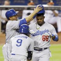Photo - Los Angeles Dodgers' Yasiel Puig (66) celebrates with teammates Dee Gordon (9) and Miguel Olivo, rear left, after hitting a three-run home run, scoring them all, during the fourth inning of a baseball game against the Miami Marlins, Saturday, May 3, 2014, in Miami. (AP Photo/Wilfredo Lee)