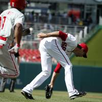 Photo - Washington Nationals starting pitcher Doug Fister (58) fields the sacrifice bunt by Philadelphia Phillies' Jimmy Rollins (11), who was out at first base on the play, during the first inning of a baseball game at Nationals Park Thursday, June 5, 2014, in Washington. (AP Photo/Alex Brandon)