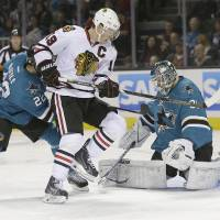 Photo - San Jose Sharks goalie Antti Niemi (31), of Finland, blocks a shot against Chicago Blackhawks center Jonathan Toews (19) during the second period of an NHL hockey game in San Jose, Calif., Saturday, Feb. 1, 2014. (AP Photo/Tony Avelar)