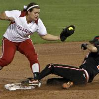 Photo - OU / OSU / COLLEGE SOFTBALL: Oklahoma's Georgia Casey (42) gets an out on Oklahoma State's Kelsey Anchors (19) during the Bedlam softball game between the University of Oklahoma Sooners and the Oklahoma State University Cowgirls at ASA Hall of Fame Stadium on Wednesday, March 28 2012, in Oklahoma City, Oklahoma.  Photo by Chris Landsberger, The Oklahoman