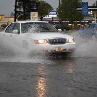 Photo - Cars travel through high water on W Lindsey Street near McGee Drive during a thunderstorm in this 2011 file photo. THE OKLAHOMAN ARCHIVES  Sarah Phipps