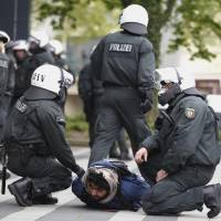 Photo -   Police detain a protestor during a demonstration of Salafists in Solingen northwestern Germany, Tuesday, May 1, 2012. Police spokeswoman Anja Meis said a group of Salafists protesting against a far-right march threw stones and attacked officers separating the two rallies. Three policemen and a passer-by were injured. Meis said the violence erupted after far-right protesters showed cartoons depicting Islam's Prophet Muhammad drawn by Danish cartoonist Kurt Westergaard which were first published in a newspaper in 2005. Islamic law generally opposes any depiction of the prophet. (AP Photo/dapd, Roberto Pfeil)