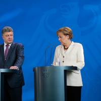 Photo - German Chancellor Angela Merkel, right, and Ukraine president-elect Petro Poroshenko attend a joint news conference prior to a meeting at the chancellery  in Berlin, Thursday, June 5, 2014. (AP Photo/Markus Schreiber)