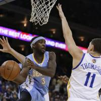 Photo - Denver Nuggets' Ty Lawson, left, looks to pass away from Golden State Warriors' Klay Thompson (11) during the first half of an NBA basketball game Wednesday, Jan. 15, 2014, in Oakland, Calif. (AP Photo/Ben Margot)