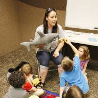 Photo - Instructor Amanda Williams describes living habits of the stuffed animals students brought to summer camp at the Oklahoma City Zoo watching a sea lion at Aquaticus in Oklahoma City Wednesday, June 26, 2013.  Photo by Paul B. Southerland, The Oklahoman