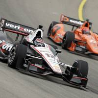 Photo - Will Power (12) races Simon Pagenaud, right, during practice for the IndyCar Series' Iowa Corn Indy 300 auto race, Friday, July 11, 2014, at Iowa Speedway in Newton, Iowa. (AP Photo/Charlie Neibergall)
