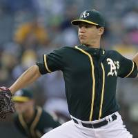 Photo - Oakland Athletics' Tommy Milone works against the Washington Nationals in the first inning of a baseball game on Friday, May 9, 2014, in Oakland, Calif. (AP Photo/Ben Margot)