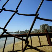Photo - FILE - In this Monday, May 5, 2003 file photo deserted hotels in an area used by the Turkish military are seen through a wire fence in the Turkish-occupied area in the abandoned coastal city of Varosha,  in southeast of the island of Cyprus.  Time virtually stopped in 1974 for the Mediterranean tourist playground of Varosha. When Turkey invaded Cyprus in the wake of a coup by supporters of union with Greece, thousands of residents fled, and chain-link fences enclosed a glamorous resort that it's said once played host to Hollywood royalty like Elizabeth Taylor.    (AP Photo/Petros Karadjias, file)