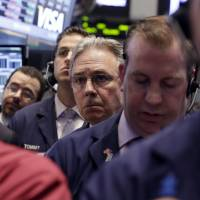 Photo -  Thomas Kaye, third from right, works Friday with fellow traders on the floor of the New York Stock Exchange.  AP Photo   Richard Drew -  AP