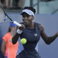 Photo - Venus Williams returns the ball to Victoria Azarenka, from Belarus, during the first set of their match in the Bank of the West Classic tennis tournament in Stanford, Calif., Thursday, July 31, 2014. (AP Photo/Jeff Chiu)