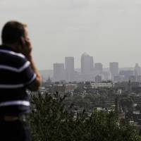 Photo -   FILE In this Friday, Sept. 23, 2011 file photo a man talks on a mobile phone as the hi-rise buildings of the banks based in the Canary Wharf business district are seen in the distance from Parliament Hill on Hampstead Heath in London. British officials have given their word: 'We won't read your emails.' But experts say that its proposed new surveillance program, unveiled last week as part of the government's annual legislative program, will gather so much data that spooks won't have to read your messages to guess what you're up to. (AP Photo/Matt Dunham)