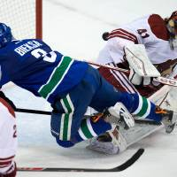 Photo - Vancouver Canucks' Kevin Bieksa, centre, scores the winning goal against Phoenix Coyotes' goalie Mike Smith, right, as Michael Stone watches during an NHL hockey game in Vancouver, British Columbia, on Sunday, Jan. 26, 2014. (AP Photo/The Canadian Press, Darryl Dyck)