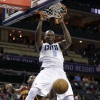 Photo - Charlotte Bobcats' Bismack Biyombo (0) dunks past Cleveland Cavaliers' Tristan Thompson (13) during the first half of an NBA basketball game in Charlotte, N.C., Wednesday, April 17, 2013. (AP Photo/Chuck Burton)