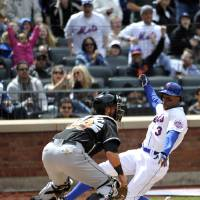 Photo - New York Mets' Curtis Granderson (3) scores at home plate past Miami Marlins catcher Jarrod Saltalamacchia on a double by David Wright in the fifth inning of a baseball game at Citi Field on Sunday, April 27, 2014, in New York. (AP Photo/Kathy Kmonicek)