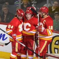 Photo - Calgary Flames' Mike Cammalleri, centre, celebrates his goal against the Vancouver Canucks with Jarome Iginla, right, and Jiri Hudler, of the Czech Republic, during first period NHL action in Calgary on Sunday, March 3, 2013. (AP Photo/The Canadian Press, Larry MacDougal)