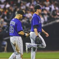 Photo -   Colorado Rockies starting pitcher Drew Pomeranz flexes his right leg after being hit by a line drive from San Diego Padres batter Edinson Volquez during the second inning of a baseball game Monday, May 7, 2012 in San Diego. The Rockies' Marco Scutaro walks with Pomeranz. (AP Photo/Lenny Ignelzi)