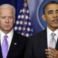 Photo - President Barack Obama stands with Vice President Joe Biden as he makes a statement Wednesday, Dec. 19, 2012, in the Brady Press Briefing Room at the White House in Washington, about policies he will pursue following the massacre at Sandy Hook Elementary School in Newtown, Ct. Obama is tasking Vice President Joe Biden, a longtime gun control advocate, with spearheading the effort. (AP Photo/Charles Dharapak)