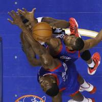 Photo - Memphis Grizzlies' Zach Randolph, top left, gets a shot past Philadelphia 76ers' Thaddeus Young, center, and Henry Sims during the first half of an NBA basketball game, Saturday, March 15, 2014, in Philadelphia. (AP Photo/Matt Slocum)